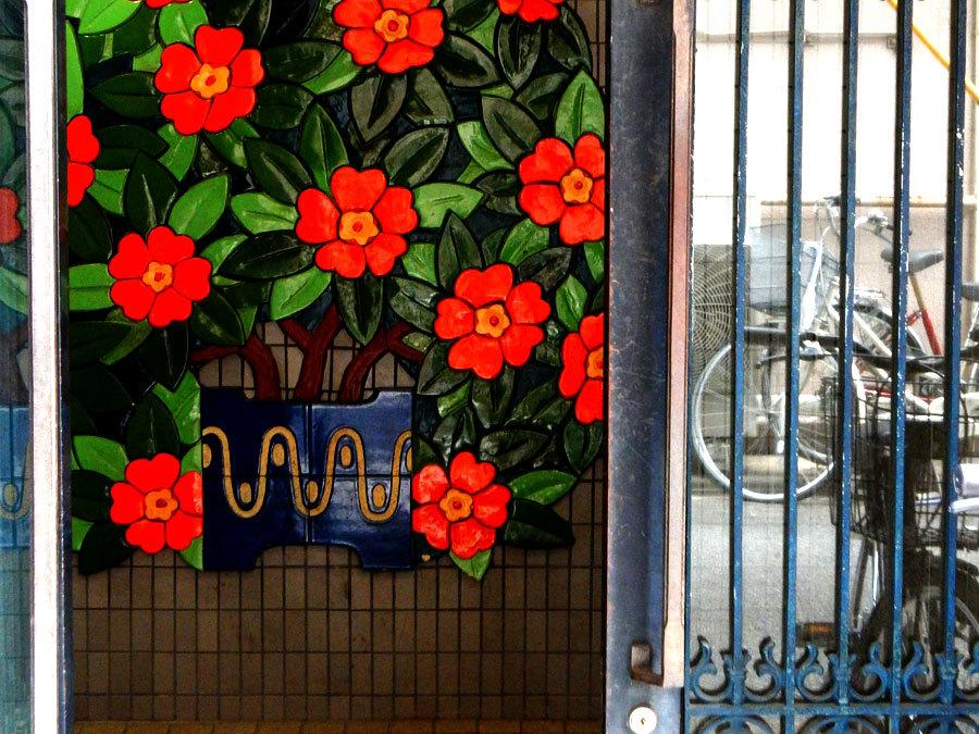 壁にへばりついた赤い花