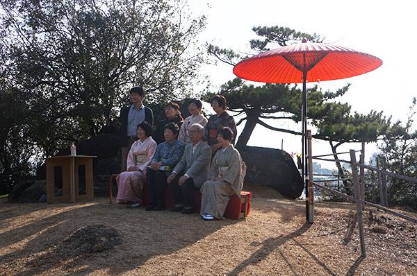 明神鼻のお菊明神の祠前で、陶芸家・清水氏ご夫妻を囲んでスタッフの記念撮影